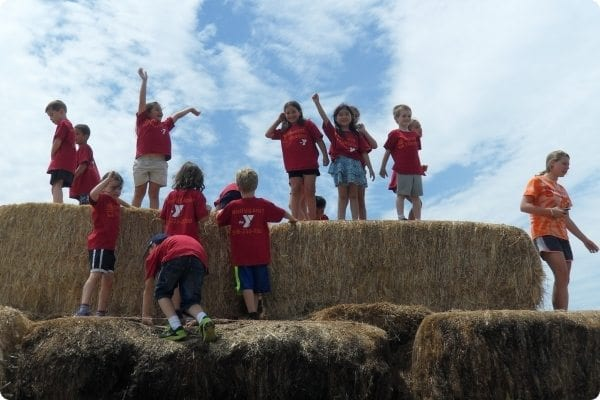 Counselors and campers standing on hay